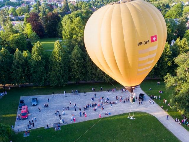 Luftballon unten hängt ein Akrobat