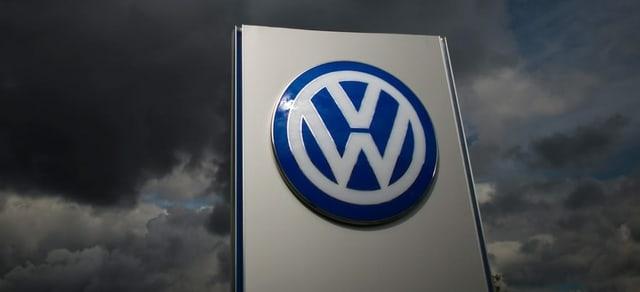 VW-Logo im Hintergrund dunkle Gewitterwolken