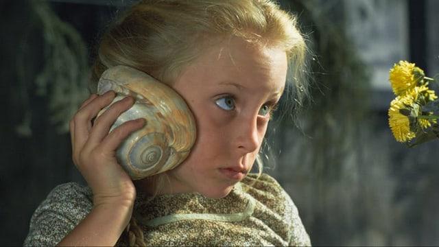 Ein blondes Mädchen hält eine Muschel an sein Ohr.