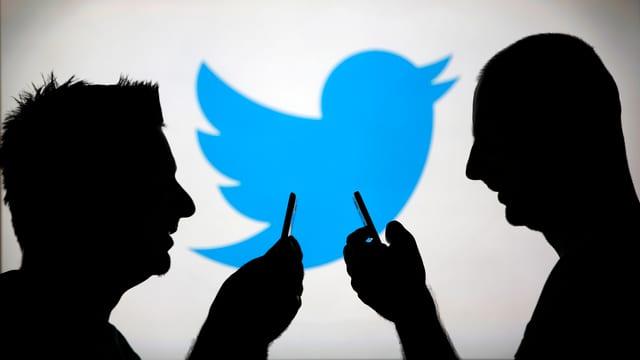 Zwei Personen sind im Profil abgebildet wie sie auf ihre Smartphones schauen im Hintergrund ist gross das Twitter-Logo zu sehen.