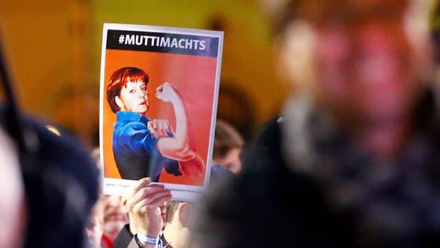 Jemand hält an einer Wahlveranstaltung ein Bild von Merkel mit Muckis hoch, auf dem steht #Muttimachts.