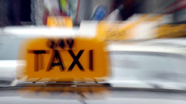 """Verwischtes Foto von gelben Taxischildern mit Aufschrift """"Taxi"""" auf Autodächern"""