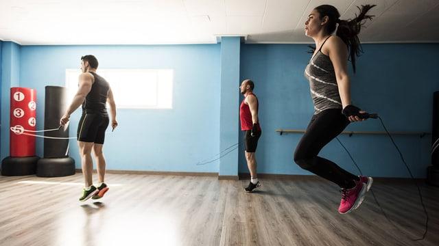 Junge Sportler mit Springseilen, alle drei in der Luft
