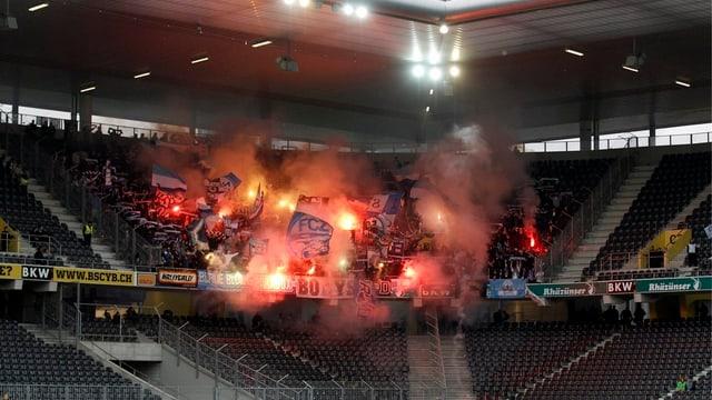 Fans im Stadion mit brennenden Fackeln.