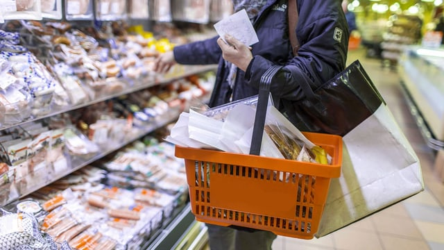 Eine Frau mit Einkaufskorb und Einkaufszettel steht vor einem Regal