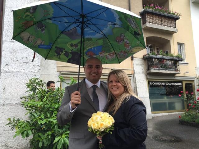 Frisch Vermählte unter einem farbigen Regenschirm