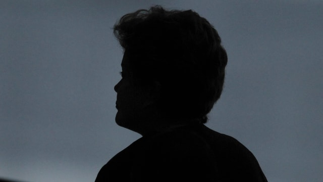 Kopf einer Frau als Silhouette vor dunklem Hintergrund