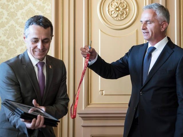 Trais purtrets e la clav dal departament da l'exyteriur surdà Didier Burkhalter ad Ignazio Cassis.