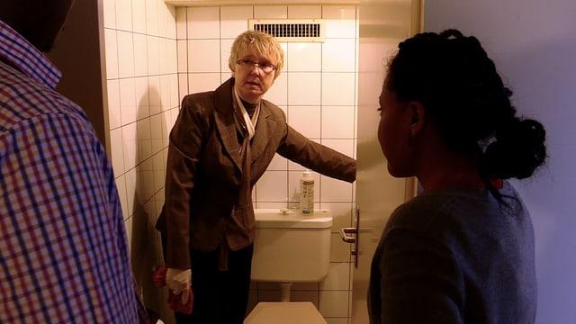 Ein Mann zeigt zwei Personen eine Toilette.