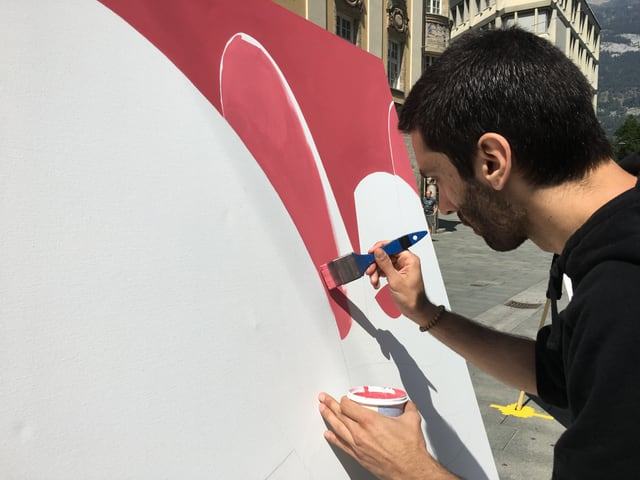 Künstler malt mit Pinsel auf Leinwand