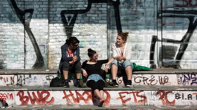 Drei Frauen sitzen vor einer steinernen Wand mit Graffities und geniessen den Sonnenschein.