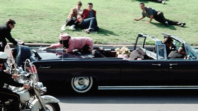 Jackie Kennedy lehnt sich über ihren getroffenen Gatten John.