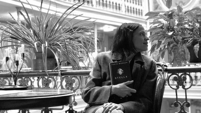 Annette König sitzt in einem Grand Hotel und hält «Stella» in der Hand