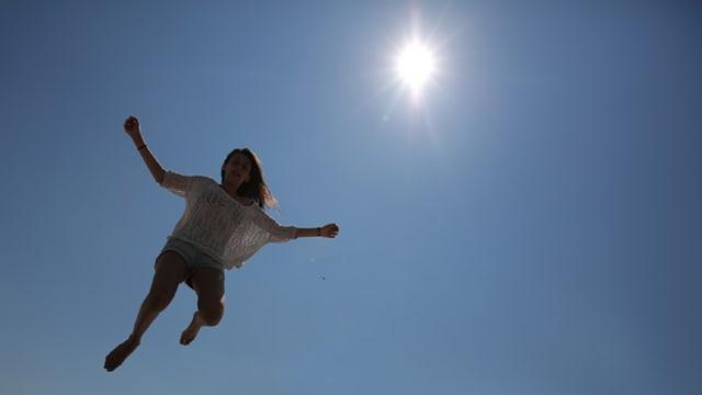 Mädchen springt in die Luft, die Sonne scheint.