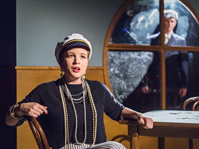 Haupdarstellerin Anna Kovach sitzt mit Kapitänsmütze am Tisch.