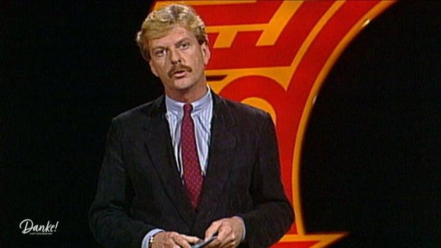 Kurt Aeschbacher in einem schwarzen Anzug mit roter Kravatte.