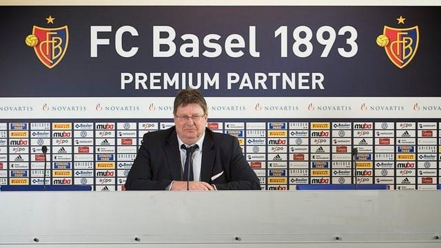 Ein Mann sitzt vor FCB-Logo