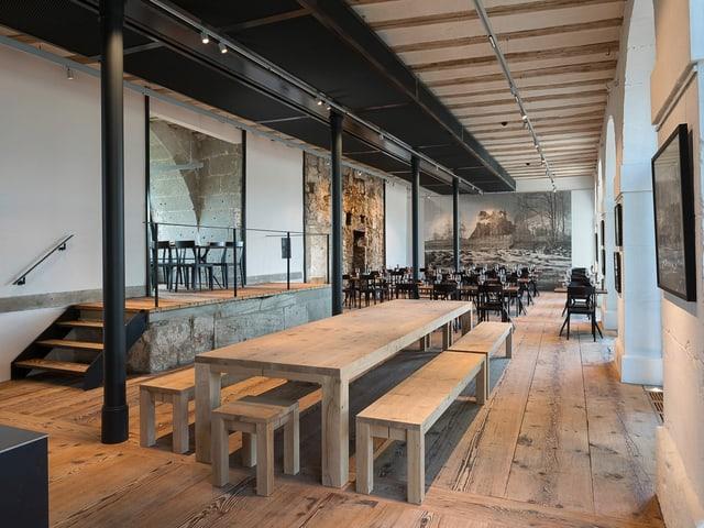 Saal mit langem Holztisch, dahinter kleinere Tische, an einer Wand sieht man einen Rundbogen aus alten Steinblöcken