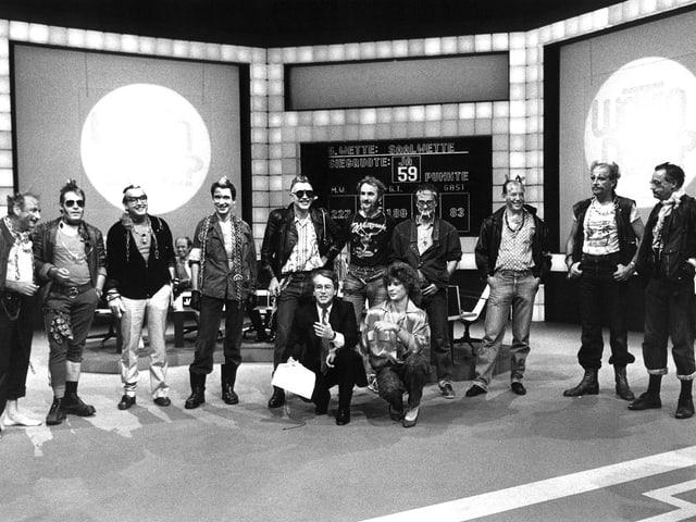 Frank Elstner mit einer Wettkandidatin. Auf der Bühne stehen 10 als Punks verkleidete Banker.