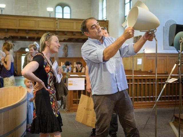 Mann zeigt einer Frau eine weisse Lampe.