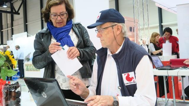Eine Frau links im Bild mit einem Papier in der Hand, rechts von ihr ein Mann des Vereins Computerias sitzend an einem Computer.