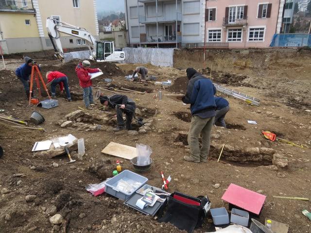 Mitarbeitende beim Freilegen und Dokumentieren der Gräber.
