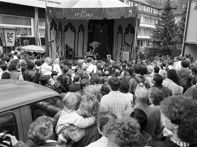 Viele Menschen und eine Bühne auf einem alten Bild.