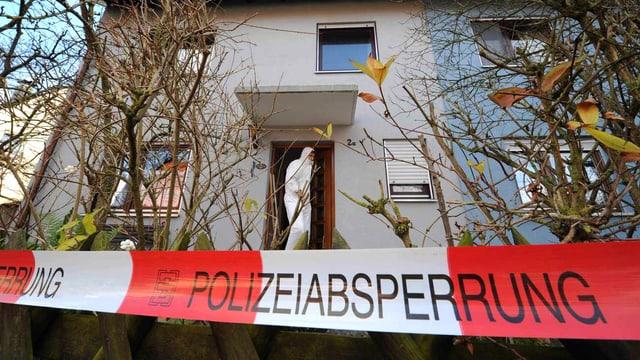 Ein Polizeiabsperrung vor einem Haus, ein Mann von der Spurensicherung steht in der Tür.