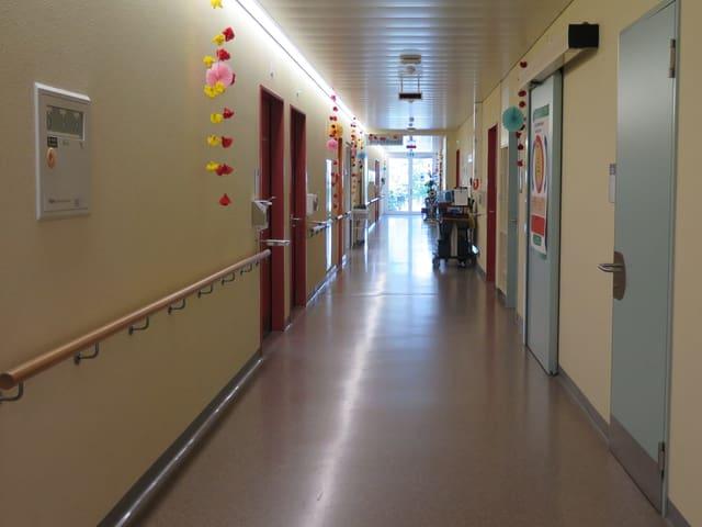 Ein Spitalgang mit verschiedenen Zimmertüren.