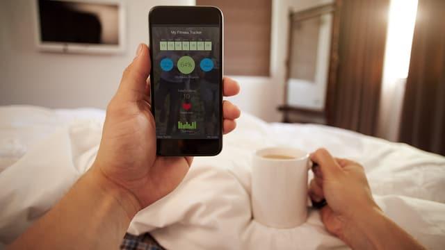 Mann schaut Smartphone mit Vitaldaten im Bett an.