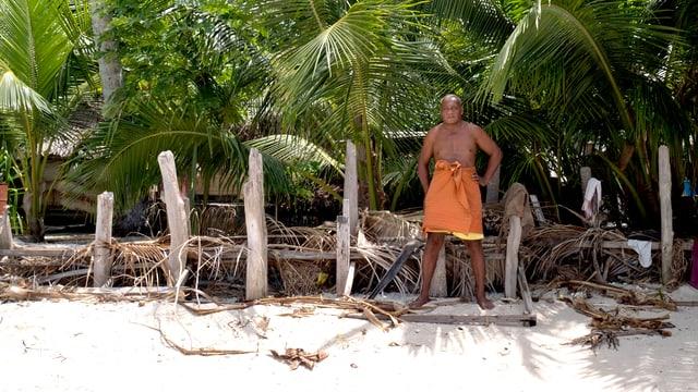 Ein Mann steht vor einem Palmenzaun.
