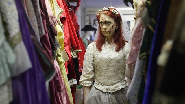Eine Dame im Brautkleid mit künstlichem Blut im Gesicht steht zwischen Kostümen