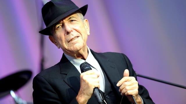 Der Musiker Leonard Cohen singt auf der Bühne mit einem Mikrophon in der Hand.