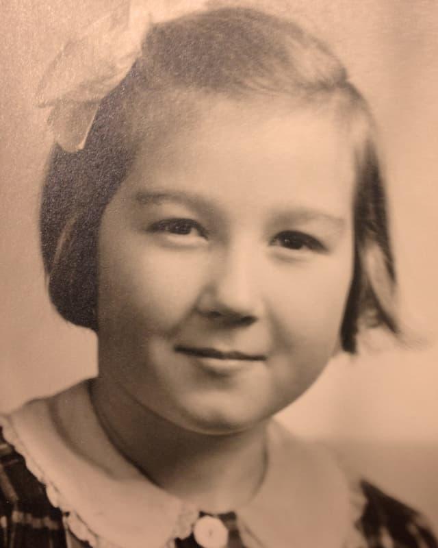 Nostalgische Fotografie eines kleinen Mädchens mit einer grossen Schleife in den Haaren.