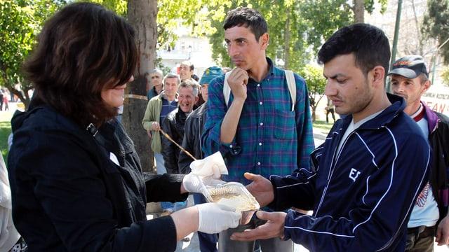 Eine Frau übergibt einem Mann eine Aluschale mit Essen.