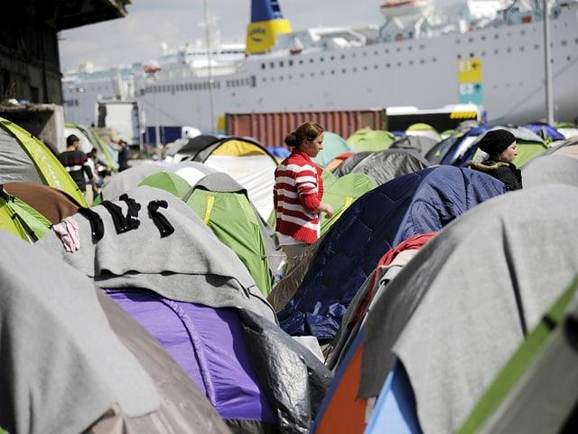 Am Hafen von Piräus stehen Dutzende Zelt. Dahinter hat ein grosses Passagierschiff angelegt. (reuters)