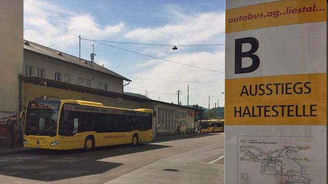 Haltestellentafel Bus im Vordergrund, im Hintergrund steht ein Bus, am Bahnhof Liestal.