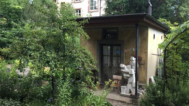 Blich durch einen Garten auf ein kleines Atelierhaus