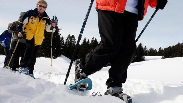 Eine Gruppe von Menschen laufen mit Schneeschuhen im Schnee.
