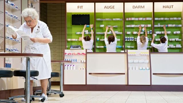 5 Frauen in Kitteln in einer Apotheke, eine liest eine Liste, die anderen füllen Regale auf.