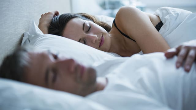 Eine schlafende Frau und ein schlafender Mann liegen in einem Bett.
