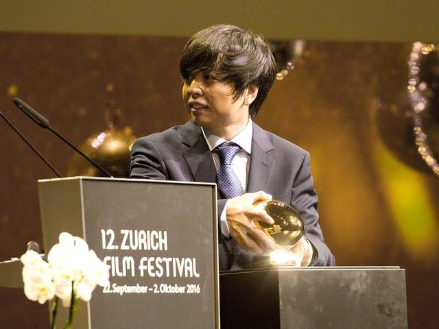 Preisträger Jero Yun nimmt das goldene Auge in seine Hände.