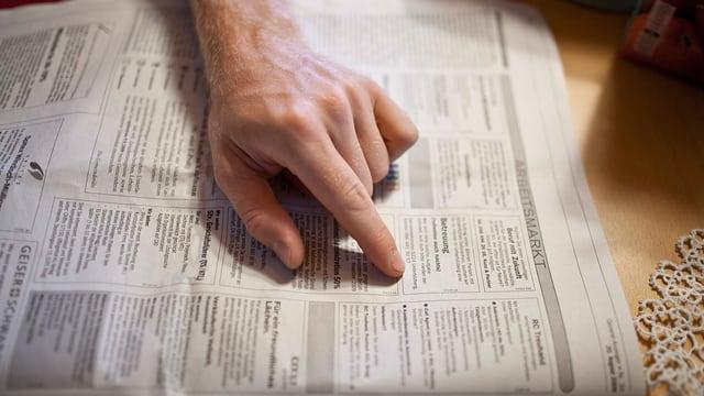 Die Hand eines jungen Mannes fährt in der Zeitung über die Stelleninserate.