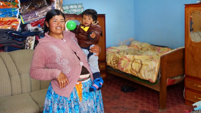 Eine bolivianische Frau trägt ihr Kleinkind auf dem Arm.