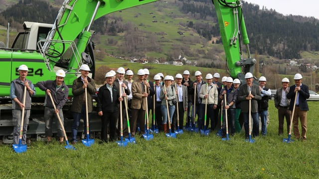 Ina retscha persunas cun cappellina ed ina pala stattan davant in grond excavatur. El funs ves'ins il vitg da Schluein.