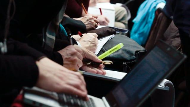 Nahaufnahme: Menschen in Sitzreihe machen Notizen auf Papier und tippen auf Laptops