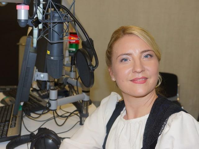 Frau in Tracht vor Microfon in Radiostudio.