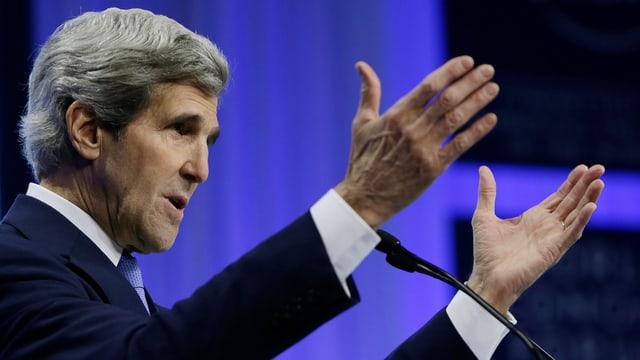 John Kerry an einem Mikrofon, er streckt beide Arme aus.