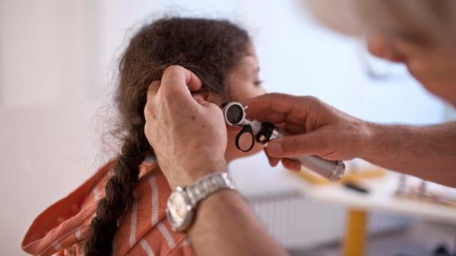 Ein Arzt schaut einem Mädchen mit dem Othoskop ins schmerzende Ohr.