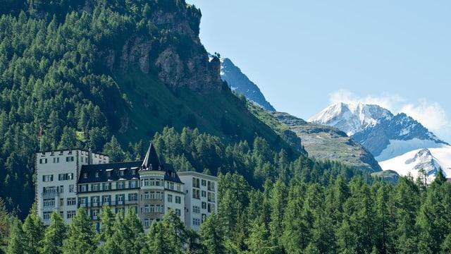 Ein altes, grosses Hotel in einem Wald. Nahe an einem schneebedeckten Gipfel.